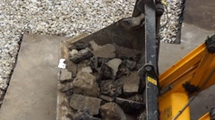 Excavator filled with broken asphalt in the yard near the pit filled with gravel Stock Footage