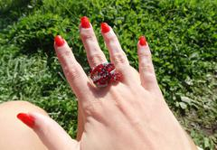 ring jewellery with red ruby crystals on finger - stock photo