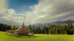 Time lapse clouds moving over beautiful mountain landscape with hay stack  Stock Footage