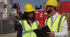 An African American woman discussing logistics with a manager at a shipyard. Sho - stock footage