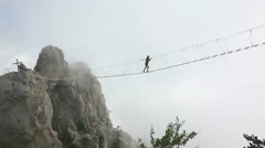 Young Girl walking on tight rope bridge over the abyss - stock footage
