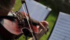 A female musician playing a violin in an orchestra. Close-up detail shot. Stock Footage