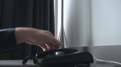 Man hand closeup dial on telephone keyboard a number, hold the receiver, talk Stock Footage