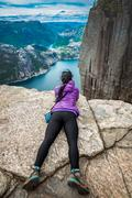 Stock Photo of Prekestolen. Woman looking at the landscape from a height.