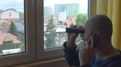 Young man spy using binoculars for see neighborhood closer, mobile phone talking Stock Footage