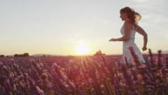 SLOW MOTION: Young woman running through lavender field at sunset Stock Footage