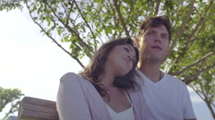 Cute Young Couple Relax On A Bench Together On Summer Day In The Park Stock Footage