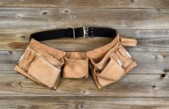Leather tool belt on rustic wooden boards Stock Photos