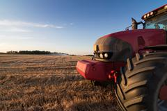 Agriculture tractor on a stubble field Stock Photos