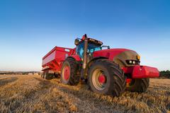 Agriculture tractor and trailer on a stubble field Stock Photos