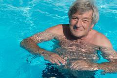 Active senior swimming - stock photo