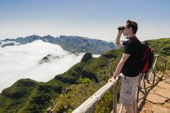 Stock Photo of Man looking into binoculars in Madeira viewpoint