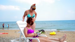 Redhead girl on the beach reading a book, while the second looks Stock Footage