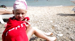 girl in a towel sitting on the rocky beach - stock footage