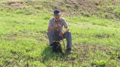 Old man - shepherd sitting in the meadow with dog and keeping herd, 4k Stock Footage