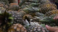 Hand selecting fresh Pineapple in Slow Motion Stock Footage