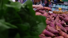 Consumer selecting sweet potatoes at the supermarket in Slow Motion Stock Footage