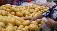 Consumers selecting potatoes at the supermarket in Slow Motion Stock Footage