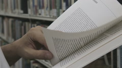 Reading a book at the library Stock Footage