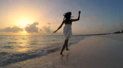 Young barefoot ethnic female in white dress dancing on sunset beach - stock footage