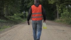 Man walking away with plastic can - stock footage