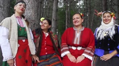 Women dressed in Bulgarian folk costumes surrounded by trees Stock Footage