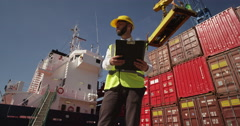A young foreman doing inspection rounds through an industrial harbor.RE Stock Footage