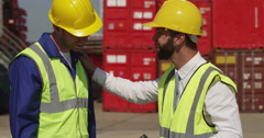 A docker and a supervisor celebrate with a high five at an industrial harbor. Stock Footage