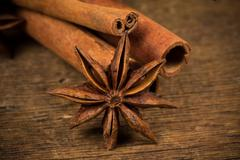 Close up of cinnamon sticks and star anise on wood - stock photo