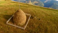 Flying over mountain landscape with hay stack at meadow Stock Footage