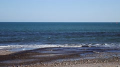 Rock and beach at Stonehaven bay on sunny day, Aberdeenshire, Scotland, UK Stock Footage
