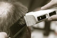 Man having a haircut with a hair clippers Stock Photos