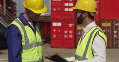 A dock worker and his supervisor at an industrial harbor. Shot on RED Epic. Stock Footage