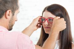 A young woman tries on glasses to the optician Stock Photos