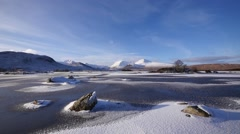 Frozen lochan in sunlight Stock Footage
