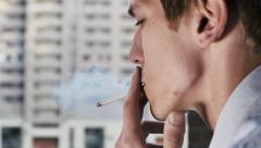 Young Man smoking cigarette closeup Street background Stock Footage
