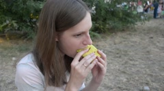 Woman eats a sandwich at a picnic Stock Footage