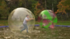 Children  having fun in inflatable water balls in park,  slow motion. Stock Footage
