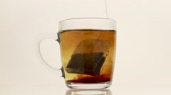 Tea bag in hot water on the white background Stock Footage