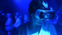 An Old Woman using Virtual Reality glasses at technology show - stock footage