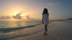 African American girl in white sundress barefoot on sunrise beach Stock Footage