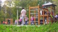 Children and parents having fun on playground in park. Footage