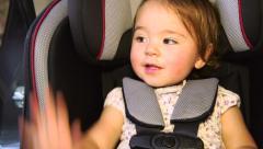 Toddler girl buckling her car seat belt and waving bye bye Stock Footage