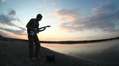 Street musician takes his guitar and starts playing at sunset the sun goes down Stock Footage