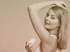Girl applying stick deodorant in armpit. - stock photo
