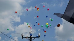 Children realese free in cloudy sky blue red white green balloons summer. - stock footage