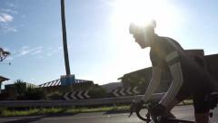 Cyclists pass as one rides up a hill slow motion Stock Footage