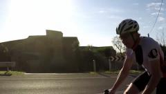 Stock Video Footage of Cyclist rides up hill and past camera MS slowmotion