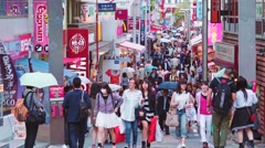 People walk and shop along Takeshita Street in Harajuku, Tokyo, Japan Stock Footage