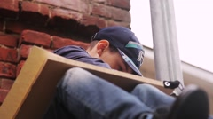 The boy in the cap draws on an easel sitting on the stone stairs in the sky Stock Footage